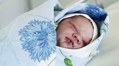 Swaddled newborn baby open eyes, lay on table in maternity hospital in blue Stock Footage