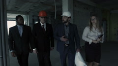 Woman, men in suit and helmet walk, discuss, communicate. Female with tablet is Stock Footage