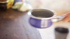 Pouring water from jug into saucepan Stock Footage