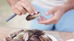 Removing freshly cooked mussels from shells - stock footage