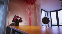 View of room with bouquet of flowers, many red helium air balloons. Little Stock Footage