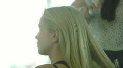 Hairdresser styling woman's hair with hairspray Stock Footage