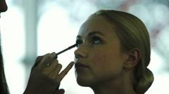 Makeup artist applying mascara on women's eyelashes Stock Footage