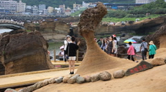 Tourists taking photos with amazing Queen's Head hoodoo stone in Yehliu Geopark Stock Footage
