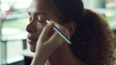 Makeup artist applying eye shadow on women's eyes Stock Footage