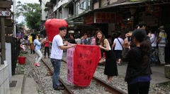 People preparing and launching chinese lanterns that people write their wishes Stock Footage
