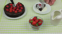 Man eating a cream covered strawberry chocolate fudge cake Stock Footage