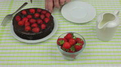Mans hands cutting a strawberry topped chocolate fudge cake Stock Footage