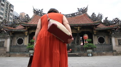 Woman in red bowing before entering the Lungshan Temple in Taipei Stock Footage