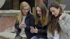 Teens Look At Their Smartphones, Girl Shakes Hers, And They All Laugh Arkistovideo