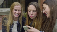 Closeup Of Group Of Friends Looking At A Smartphone, They Act Silly And Laugh - stock footage