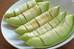 peel cantaloupe melon in white plate - stock photo