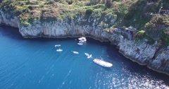 AERIAL FLY BY BLUE GROTTO CAVE NEAR BLUE OCEAN WITH LOCAL BOATS Stock Footage