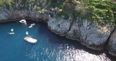 AERIAL SHOT SUNLIGHT REFLECTION OFF BLUE OCEAN WITH LOCAL TOURIST BOATS - stock footage