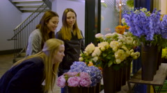 Funny Teen Girls Coordinate Smelling Flowers At A Market, As A Funny Joke - stock footage