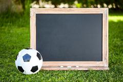 Football and blackboard on the grass of the pitch - stock photo