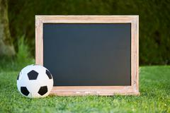Football and blackboard on the grass of the pitch Stock Photos