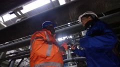 4K Low angle view male & female engineers in power station discussing operations - stock footage