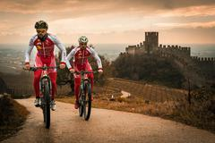 Cyclists train on the hills surrounding the castle of Soave. - stock photo