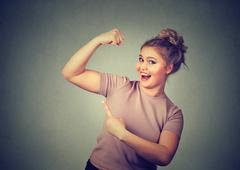 Young happy woman flexing muscles showing her strength. Weight loss concept Stock Photos