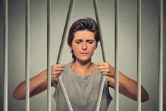 Stressed desperate sad woman bending bars of her prison cell Stock Photos