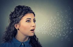 Woman talking with alphabet letters coming out of her mouth. Communication, i - stock photo