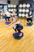 Dedicated group trains squats on half ball at fitness gym Kuvituskuvat