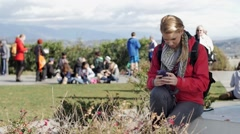 Backpacking woman texts in public - stock footage