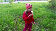 Child girl blows away dandelion fluff with. - stock footage