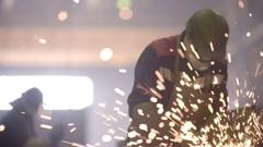 Worker using industrial grinder on metal parts in industrial workshop warehouse Stock Footage