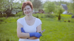 Portrait of pretty woman with pruner in her garden Stock Footage