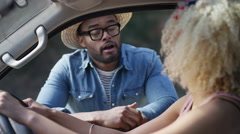 4K Hipster guy giving directions to woman through the open window of her car Stock Footage