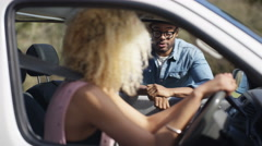 4K Hipster guy chatting to young woman through the open window of her car Stock Footage