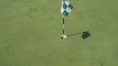 A golf ball rolling into the hole on a sunny day. - stock footage