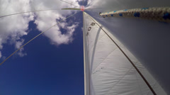 Yachts sails billow in the wind against blue sky sailing on the ocean Stock Footage