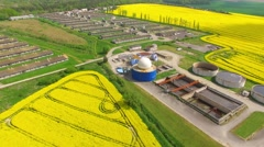 Biogas plant from pig farm in green fields. - stock footage