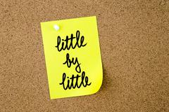 Little By Little written on yellow paper note Stock Photos