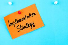Implementation Strategy written on orange paper note Stock Photos