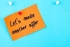 Lets Make Another Offer written on orange paper note Stock Photos