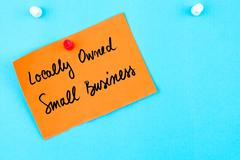 Locally Owned Small Business written on orange paper note - stock photo