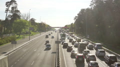 Line of cars stuck in traffic jam on sunny day, ambulance trying to make its way - stock footage