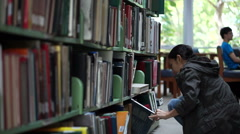 Female, Asian girl student stand searching bookshelves, reading books - stock footage