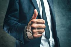 Gaining bosses approval, businessperson gesturing thumb up Stock Photos