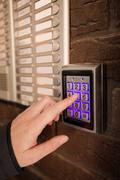 Woman dialing passcode on security keypad intercom - stock photo