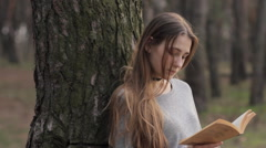 Teen girl reading book leaning against tree trunk in woods in early spring Stock Footage