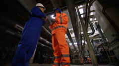 4K Low angle view male & female engineers in power station discussing operations Stock Footage
