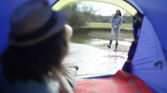 4K Young hipster guy watching his girlfriend from his tent on camping trip - stock footage