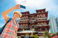 Smiling young woman making selfie near Buddha Tooth Relic Temple - stock photo