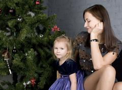 Happy family at christmas tree sitting home smiling, waiting for father at Stock Photos