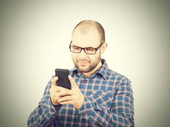 Caucasian man typing a message on mobile phone. - stock photo